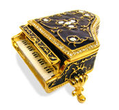 Ornate grand piano keys. Photo of a beautiful ornate grand gold piano encrusted with diamonds on the lid and decorated with flowers Stock Photo