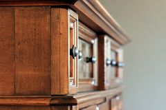 Ornate handles on wooden cabinet Royalty Free Stock Image