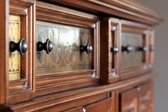 Ornate handles on wooden cabinet Stock Photo
