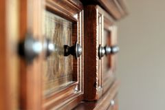 Ornate handles on wooden cabinet Royalty Free Stock Images