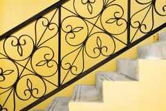 Ornate handrail of wrought iron. With yellow wall royalty free stock image
