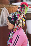 Ornate Headwear of Hani People. A Hani woman look out across the busy market wearing an elaborate and colorful hat with beads and old coins Royalty Free Stock Photography