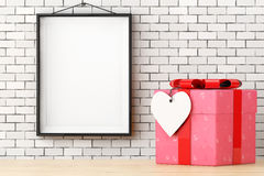 Ornate with Hearts Paper Gift Box with Heart Tag in front of Bri. Ck Wall with Blank Frame extreme closeup. 3d Rendering Royalty Free Stock Image