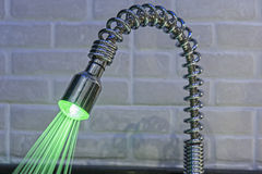 Ornate iluminated tap in kitchen Royalty Free Stock Image