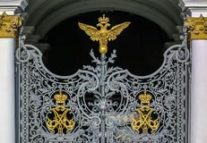 Ornate iron gate of Winter Palace Hermitage in Saint Petersburg, Russia with Russian coat of arms of imperial double headed eagle. And monograms of Emperor royalty free stock photo
