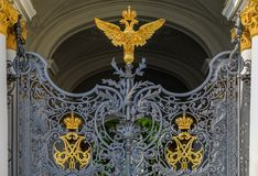 Ornate iron gate of Winter Palace Hermitage in Saint Petersburg, Russia with Russian coat of arms of imperial double headed eagle. And monograms of Emperor royalty free stock photography