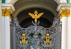 Ornate iron gate of Winter Palace Hermitage in Saint Petersburg, Russia with Russian coat of arms of imperial double headed eagle. And monograms of Emperor royalty free stock image