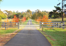 Ornate Iron gates. Locked ornate wrought iron gates protecting a country property from intruders with tarmac driveway in a colourful autumn rural setting Stock Photos