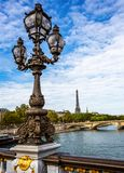 Ornate lamp on the Alexander III Bridge with the Eiffel Tower in the background in Paris royalty free stock photos