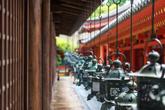 Ornate lanterns at Kasuga Grand Shrine. Detail of a row of ornate bronze lanterns, donated by worshipers, at the red Kasuga Grand Shrine in the city of Nara Stock Images