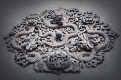 Ornate low relief sculpture of dragon on wall. Stock Photo