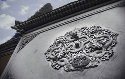Ornate low relief sculpture of dragon on wall. Royalty Free Stock Image