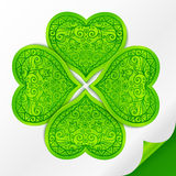 Ornate lucky clover on paper. Green plastic ornate lucky clover on paper with curved corner Royalty Free Stock Images