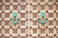 Ornate medieval door with two turquoise handles Stock Photos
