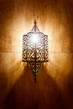 Ornate metal lamp glowing on marble wall stock photo