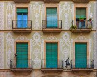Ornate painted building facade and windows with green wooden shu stock photo