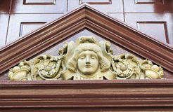 Ornate Pediment. Gold Face Carved into a painted brown Pediment Stock Photos