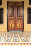 Ornate Peranakan Style Doors Entryway. Ornate Doors of Peranakan Style exterior with Chinese wood carvings and colorful tiles entrance Royalty Free Stock Photos