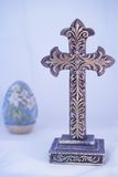 Ornate purple cross with Easter lily egg. Ornate gold filigree and purple cross has Easter lily egg in background to offer seasonal decor Stock Image
