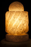Ornate rock salt lamp on black background Stock Image