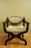 Ornate Roman Styled Chair. Against an Olive Green Wall Stock Photos