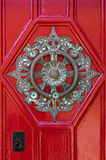 Ornate round brass door knocker. On red door royalty free stock photography