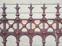 Ornate rusty iron fence. A segment of ornate fencing that is showing sings of rust Infront of a white wall stock photo