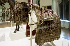 Ornate saddle with gold embroidered red cloth. On display in a museum showcase with the model of a horses visible behind Royalty Free Stock Photography