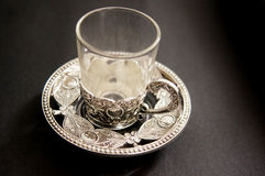 Ornate silver tea cups. Ornate silver and glass tea and coffee cups. The engravings are traditional indian designs Stock Photo