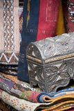 Ornate silver trinket box with colorful textiles on sale in a Moroccan Market. Essaouria, Morocco - September 2017: Ornate silver trinket box with colorful Stock Photo