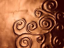 Ornate Spirals Pattern Texture. A background texture pattern of swirls and spirals indented into a copper colored metal lic surface royalty free stock photos