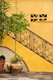 Ornate staircase and yellow walls. Ornate staircase in a courtyard with yellow walls, stone floor, and trees in pots.  Charlotte-Amalie, St. Thomas, U.S. Virgin Stock Photography