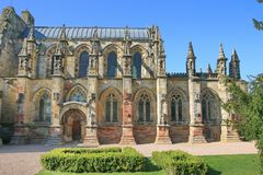 The south side of Rosslyn Chapel. Ornate stonework decorates this windows and doors at Rosslyn Chapel.  The odd asymmetrical stonework is a signature stock image