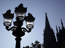 Ornate street lamp with church spires Royalty Free Stock Images