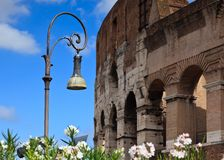 Ornate street lamp with Colosseum in background Stock Images
