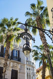 Ornate Street Lamp and Palm trees against a bright blue backgrou Stock Image