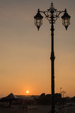 Ornate streetlamp at Sunset. An ornate streetlamp, silhouetted against the setting sun Royalty Free Stock Image