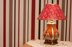 Ornate table lamp. Red and orange ornate table lamp against striped wallpaper Royalty Free Stock Image