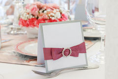Ornate table name card with pink ribbon Royalty Free Stock Images