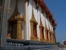 Ornate temple in Thailand. Beautiful and ornate Buddhist temple in Thailand.  The temple is white with intricate gold carvings, boddhisattva paintings and Stock Images