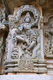 Ornate wall panel reliefs depicting Krishna dancing on the head of serpant Kalia and eventually killing him. Kedareshwara temple,. Halebidu, Karnataka, India royalty free stock photo