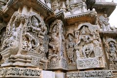 Ornate wall panel reliefs depicting from left dancing Shiva, Krishna as Kaliya-mardana and a deity and dancing Parvati, Kedareshwa. Ra temple, Halebidu stock images