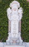 Ornate water fountain by a hedge Stock Photos