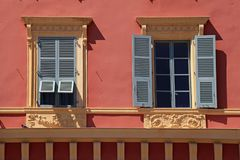 Ornate windows with grey shutters in old red stucco house, Nice, France royalty free stock images