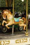 Ornate Wooden Carousel Horse. A brightly painted, ornate, festive wooden carousel horse rides up and stands out amongst other wooden rides on this merry-go-round Stock Images
