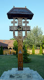 Ornate wooden cross in Bucharest church grounds, Romania. An ornately carved wooden cross beside the small church in front of where the Romanian People's royalty free stock images