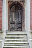 Ornate Wooden Door. Concrete steps lead to an ornately carved wooden door stock photography