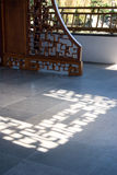 Ornate wooden screen casts interesting shadow on stone floor. Stock Photo