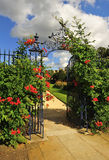 Ornate wrought iron, floral gate. An ornate wrought iron gate, festooned with flowers in a beautiful garden Royalty Free Stock Photos
