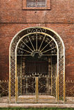 Ornate Wrought Iron Gate and Door. On a Brick Facade stock photo